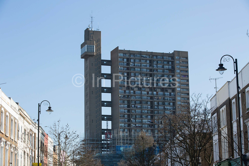 The iconic Trellick Tower overlooking Golbourne Road on the 26th March 2018 in West London, United Kingdom. Trellick Tower is Grade II listed tower block on the Cheltenham Estate in Kensal Town, London. Opened in 1972, it had been commissioned by the Greater London Council and designed in the Brutalist style by architect Ernő Goldfinger.