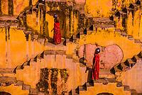 Two local women going to fetch water in Panna Meena Ka Kund step well, (baori), Amer (near Jaipur), Rajasthan, India.