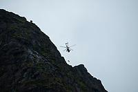 August 21, 2019: Norwegian Sea King rescue helicopter hoisting injured hiker from summit of Reinebringen mountain peak, One of Norway's most popular hikes, Reine, Lofoten Islands, Norway