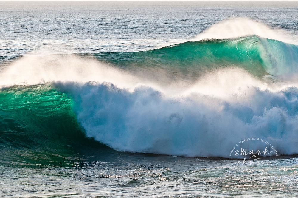 Powerful backlit waves breaking off rocky coast, Hawaii