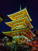 """Three-storied Koyasu Pagoda lit at night. Kiyomizu-dera (""""Pure Water Temple"""") is an independent Buddhist temple in eastern Kyoto, Japan. Otowa-san Kiyomizu-dera temple is part of the Historic Monuments of Ancient Kyoto (Kyoto, Uji and Otsu Cities) UNESCO World Heritage site. Kiyomizu-dera was founded on the site of the Otowa Waterfall in the early Heian period, in 780 by Sakanoue no Tamuramaro. Ordered by Tokugawa Iemitsu, its present buildings were built entirely without nails in 1633."""