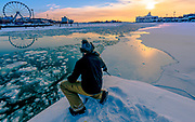 I saw this guy was trying to make a selfie of himself in an incredible sunset over the frozen gulf of Finland in Helsinki.