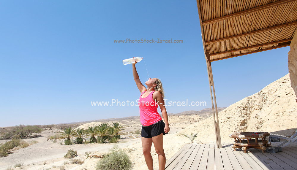 Woman refreshes herself with water after a workout in the desert. Model released