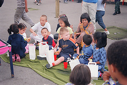 Multiracial group of primary school children sitting on rug in playground eating picnic lunches,