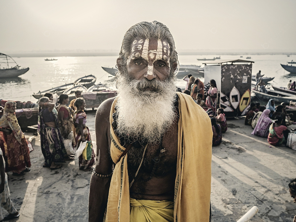 Varanasi, India - October 05, 2015: Sadhu in ghat in Varanasi. This is one of the oldest inhabited cities in the world and also the holiest of the seven sacred cities in Hinduism and Jainism and so the most important pilgrimage place for hindus. Many ascetics in Varanasi like the one in the picture wander through the ghats accepting money donations from pilgrims and foreign tourists.