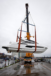 © Licensed to London News Pictures. 22/12/2012. London, UK. A 33 ton Sunseeker 68 Predator luxury yacht is lifted by crane from the Royal Victoria Dock during preparations for the 2013 Tullett Prebon London Boat Show in London today (22/12/12). . The show runs from 12th to the 20th of January 2013. Photo credit: Matt Cetti-Roberts/LNP