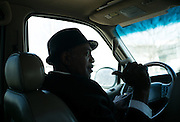 """MONTGOMERY, AL – JANUARY 25, 2016: Michael Harris, 52, carries a passenger across the city of Montgomery. In 2011, the downtown Montgomery Greyhound bus station was converted into a museum to honor the freedom riders, who endured a violent attack there in 1961. The replacement bus station, located four miles from downtown, is a prime business opportunity for independent cabbies like Mr. Harris, who make a living serving passengers unwilling to rely on city buses. Many characterize the public bus system in Montgomery as unsafe and unreliable, so wary passengers cough up $2 per mile for trips in Mr. Harris' 2005 Lincoln Navigator, traveling across town for fast food, or sometimes as far as New York City. """"This is my life,"""" Harris said. """"I love driving, and I help people out. It's just in my heart."""""""