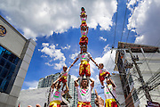 """05 JULY 2014 - BANGKOK, THAILAND: An acrobat team holds toddlers in their human pyramid on a side street in Bangkok during a parade for vassa. Vassa, called """"phansa"""" in Thai, marks the beginning of the three months long Buddhist rains retreat when monks and novices stay in the temple for periods of intense meditation. Vassa officially starts July 11 but temples across Bangkok are holding events to mark the holiday all week.    PHOTO BY JACK KURTZ"""