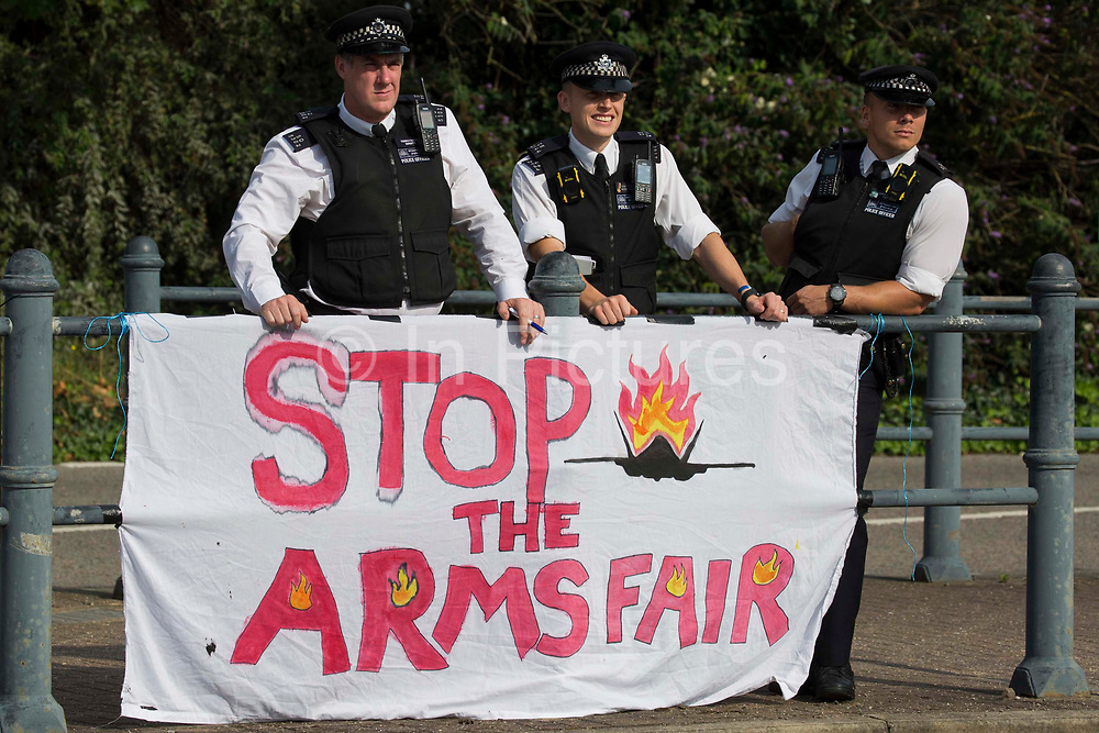 Metropolitan Police officers stand behind a Stop The Arms Fair banner outside ExCeL London as preparations for the DSEI 2021 arms fair take place on 6th September 2021 in London, United Kingdom. The first day of week-long Stop The Arms Fair protests outside the venue for one of the worlds largest arms fairs was hosted by activists calling for a ban on UK arms exports to Israel.