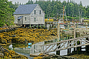 A boat house and lobster wharf piled high with traps in the tiny village of Cozy Harbor in Southport, Boothbay, Maine.