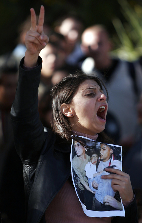 An Arab student flashes a victory sign and holds a photo of Palestinians hurt from Israeli military operatins in Gaza, during simultaneous demonstration for and against the military operation on the Gaza Strip, in front of the Hebrew University in Jerusalem, on March 3, 2008.