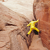 Lois Rice scrambles up sandstone slot canyon near Lake Powell, Utah.