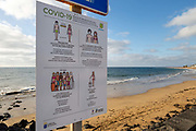 A sign with Covid-19 rules stands in front of a deserted beach in Playa Matagorda, Lanzarote, Spain on 22nd November 2020. Beaches and resorts across the island are nearly deserted since tourism plummeted due to Covid restrictions elsewhere in Europe. Although the Canary Islands have been relatively unscathed by the virus, with 155 lives lost from 2.1 million residents, the region is heavily dependent on tourism and locals are hoping that numbers recover as lockdown measures ease and vaccines potentially reduce the numbers of infections.