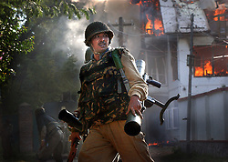 SRINAGAR, KASHMIR - SEPT. 24: Border Security Force troopers run for cover after shooting a rocket propelled grenade launcherin an effort to flush out two Muslim militants holed up inside a residential house in Srinagar, the summer capital of Jammu and Kashmir state, on September 24. Few people braved anti-poll violence in Kashmir's main city to vote in a state election after the early morning gun battle.. (Photo by Ami Vitale/Getty Images)
