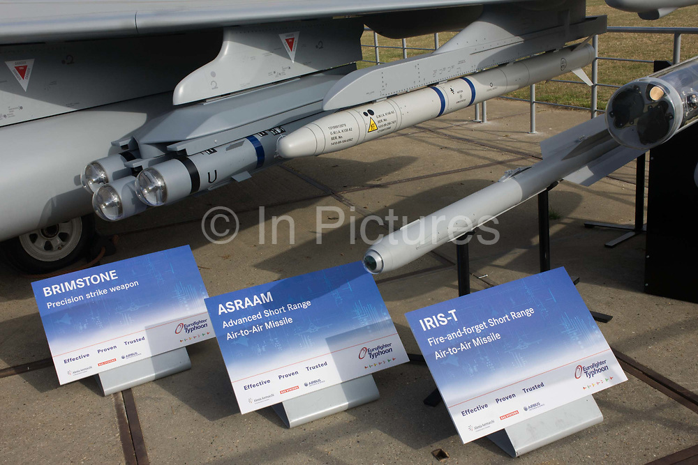 """BAE Systems Typhoon jet fighter, exhibited with missile and smart bomb systems, at the Farnborough Air Show, England. Brimstone, ASRAAM AND IRIS-T missile systems are seen in detail shown on the ground: Brimstone is an air-launched ground attack missile developed by MBDA. as is ASRAAM (Advanced Short Range Air-to-Air Missile) which is an imaging infrared homing (""""heat seeking"""") air-to-air missile. The IRIS-T (Infra Red Imaging System Tail/Thrust Vector-Controlled) is a German-led program to develop a short-range air-to-air missile to replace the venerable AIM-9 Sidewinder found in some of the NATO member countries."""