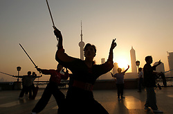 Early morning Tai Chi exercisies at dawn on The Bund in Shanghai China