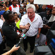 """A George Zimmerman supporter (white shirt) holds the hand of the man that yelled at him earlier in the march during the No Justice No Peace- """"March Against Gun Violence""""  walk from Lake Eola in downtown Orlando, to the Orange County Courthouse on Wednesday, July 17, 2013. The march was organized by the Modarres Law Firm and Orlando attorney Natalie Jackson, one of the attorneys for Trayvon Martins parents. (AP Photo/Alex Menendez)"""