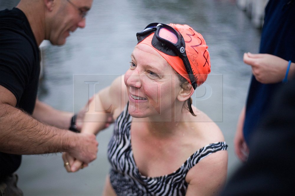 © Licensed to London News Pictures. 26/06/2011. Henley-on-Thames, UK. A competitor leaving the water at the finnish line. Swimmers take part in the Henley Swim at dawn this morning (26/06/2011). The annual event sees competitors swim the length of the 2.1km course of the Henley Royal Regatta on the River Thames, after arriving in darkness, and walking half a mile to the start at sunrise. See special instructions. Photo credit should read: Ben Cawthra/LNP