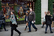 Young girl holds hands with an older man outside Selfridges, on 9th November 2017, London, England.