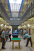 Prisoners play pool and socialise during a recreation period on C wing at the Young Offenders Institution, Aylesbury, United Kingdom. HMYOI / HM Prison Aylesbury (Her Majesty's Young Offender Institution Aylesbury) is a prison is operated by Her Majesty's Prison Service.