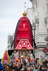 © Licensed to London News Pictures. 09/06/2013. London, UK. Followers of the Hare Krishna movement are seen with a chariot on Piccadilly, London, today (09/06/2013) as it is pulled to Trafalgar Square as part of the 'Hare Krishna' festival of 'Rathayatra'. The parade, also known as the 'Festival of Chariots', is the biggest street festival celebrated by members of the Krishna followers and, in London, features three huge, wooden chariots containing the smiling figures of Lord Jagannatha, Lady Subhadra and Lord Balarama being pulled by hand from Hyde Park to Trafalgar Square.  Photo credit: Matt Cetti-Roberts/LNP