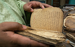 Abdel Kader Haidara looks at his family's ancient manuscripts that he is trying to preserve in his home March 6, 2007. In the past few years, with funding from different organizations including the Ford Foundation, thousands of the manscripts are being recovered, stored, preserved and studied. Sadly, many of them have been lost or severley damaged but for those that remain it is a maginificent reminder of Africa's literary history.  (Photo by Ami Vitale)
