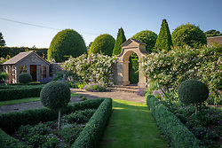 Summerhouse, topiary and stone arch with Rosa 'Sander's White Rambler' AGM and R. 'Blush Noisette' growing on the wall
