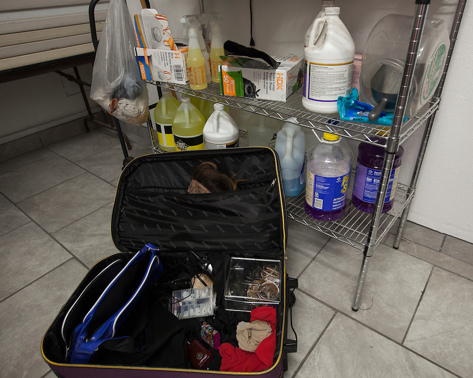 In a small storeroom in the back, a zippered suitcase of feathers and bright costumes lies on the floor under a wire shelf filled with bleach and other cleaning supplies.
