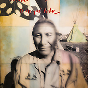 """""""Us & Them, Standing Rock #1""""  Photo shot with the """"Us & Them"""" camera in Oceti Sakowin DAPL resistance camp in Standing Rock, North Dakota, 2016. <br /> <br /> The Gentleman in the photo is Chief Arvol Looking Horse who is the Chief of the Sioux Nation. This was the first """"Us & Them"""" photo shoot in a two month stay in Standing Rock. <br /> Chief Avol Looking Horse's hand written """"Words from the Heart"""", in Lakota reads """"We are spiritual, We will survive."""" <br /> <br /> 48""""X60"""" analog print, made of 9 sheets of 16""""x20"""" gelatin silver paper, mounted in a steel frame with 5 gallons of UV acrylic resin covering the image. <br /> <br /> 1 of 2, 2016."""