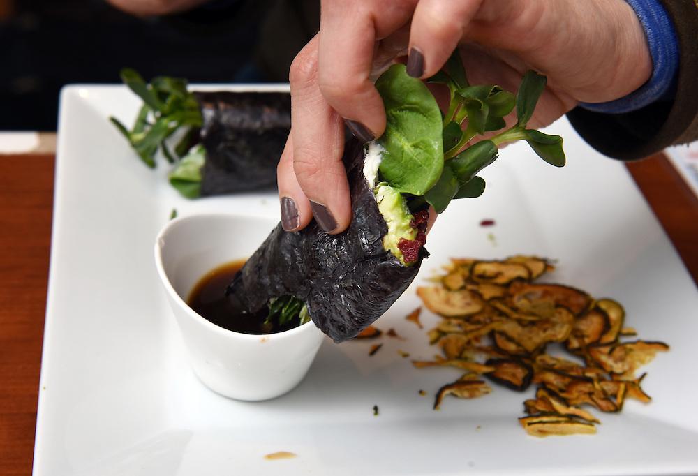 "Mara Lavitt /For Hearst Connecticut Media<br /> February 6, 2016<br /> Catch A Healthy Habit Cafe, Fairfield. Anna Kokkinos of Norwalk dips the nori wrap: nori, fig marmalade, cashew ""cheese,"" beet, sunflower sprouts, avocado, crispy onion, spinach, ""salt & vinegar"" zucchini chips."