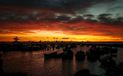 © Licensed to London News Pictures. <br /> 30/11/2016. <br /> REDCAR, UK.  <br /> A striking sunset above fishing boats in the Paddy's Hole area of South Gare with the industrial backdrop of Teesside on the last day of Autumn.<br /> Photo credit: Ian Forsyth/LNP