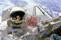 November 14, 1984 - Cape Canaveral, TX, United States of America - NASA astronaut Dale A. Gardner holds a ''For Sale'' sign referring to the two broken satellites retrieved after after completing a second spacewalk November 14, 1984 in Earth orbit. Gardner and fellow astronaut Joseph Allen working from the Discovery Space Shuttle grabbed the satellites after their Payload Assist Modules failed to fire. (Credit Image: © Nasa/Planet Pix via ZUMA Wire)