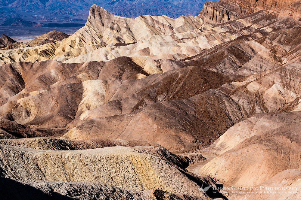 United States, California, Death Valley. Zabriskie Point is a part of Amargosa Range located in east of Death Valley, noted for its erosional landscape. View of Manly Beacon, two people walking at the path.