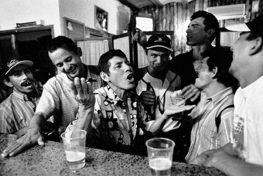 After a hard day's work in the fields, the Colombian day labourers and the businessman who hired them share some beers. Torres de Segre, Spain.