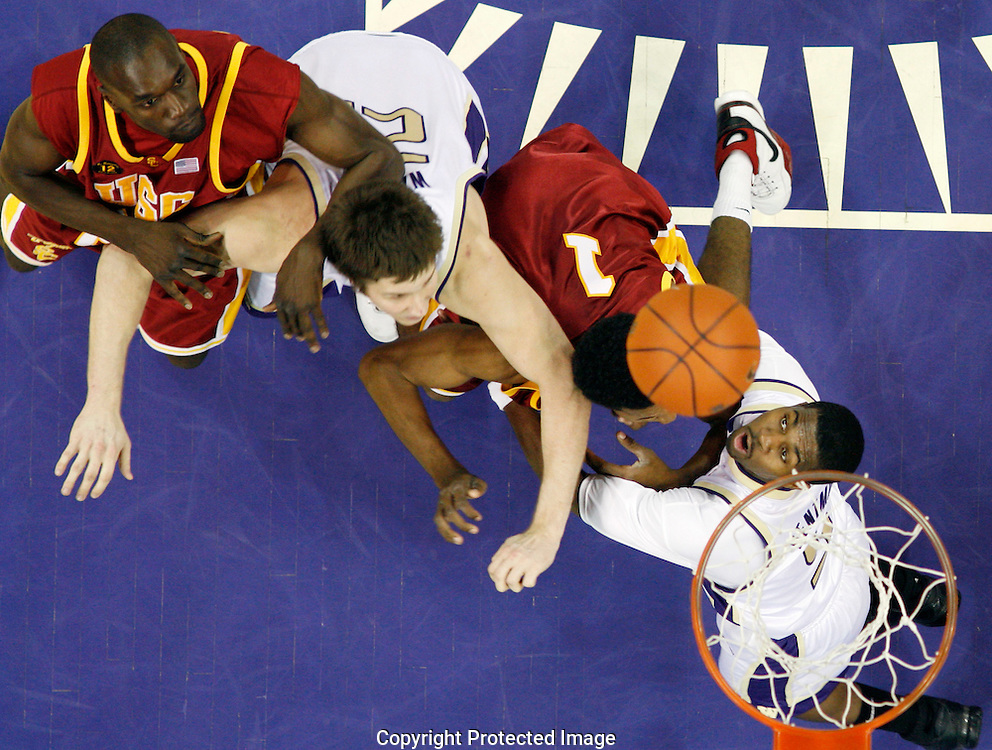 Southern California's Abdoulaye N'Diaye, left, and Nick Young (1) along with Washington's Artem Wallace, second from left, and Justin Dentmon, right, battle for a rebound. (AP Photo/John Froschauer)