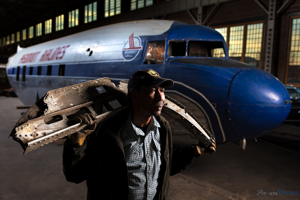 """Pilot Bill Wilkerson  is helping to rebuild an iconic DC-3 airplane at the North Carolina Transportation Museum in Spencer, NC. <br /> <br /> Photographed, Tuesday, November 21, 2017, in Spencer, N.C. JERRY WOLFORD and SCOTT MUTHERSBAUGH / Perfecta Visuals<br /> <br /> Pilot Bill Wilkerson of Pleasant Garden, North Carolina was among the first black pilots in the country. Wilkerson flew 15 years for Piedmont Airlines, which became a part of US Airways in 1989. In 1980, he became the second black person to earn the rank of captain with the company. The retired pilot still wears his captains' uniform while he gives tours at the North Carolina Transportation Museum.<br /> <br /> Wilkerson grew up in the projects of Knoxville, Tennessee with his two other siblings and his single mother, who worked as a domestic. She gave her kids the books she received from her clients.<br /> <br /> Wilkerson's mother purchased """"The Library of Universal Knowledge"""" for her children and young Bill read the chapter called """"How to Fly."""" The boy 'flew around the world' through the articles inside National Geographic and Reader's Digest. He was so intrigued, he engulfed himself in model airplanes and begged his mother for flying lessons. She initially refused, so Wilkerson and his friend paid $5 for a flying lesson at the Knoxville airport. His mother eventually gave in, and by the time he was 16 years old, Wilkerson was in flight school. Five years later, he obtained his pilot's license.<br /> <br /> Wilkerson enlisted in the Air Force and served as a mechanic until 1971. Three years later he got the job at Piedmont. While Piedmont was jokingly called the """"puddle jumper"""" airline, Wilkerson was proud to work as one of the first and few black pilots in the industry. He gained much attention as one of the few black men in uniform.<br /> <br /> Wilkerson logged more than 17,000 hours as a pilot for Piedmont. He was finally able to take his family to the places he'd only seen in the National Geog"""