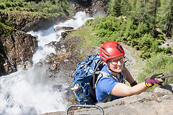 Woman climbing rock face via ferrata towards Stuibenfall Waterfall, Otztal, Tyrol, Austria