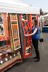 Washington DC; USA:  At the Eastern Market, one of the great markets in DC.  Woman looking at African fabrics in shop Great Zimbabwe.  Model released..Photo copyright Lee Foster Photo # 26-washdc79630