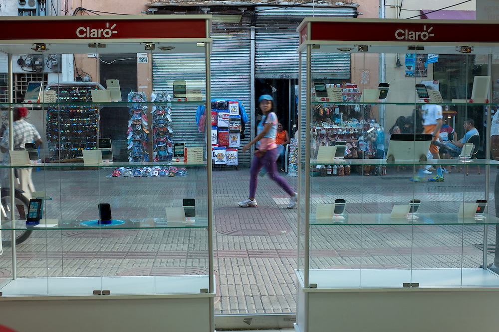 SANTO DOMINGO, DOMINICAN REPUBLIC- DECEMBER 2, 2014:  Shoppers stroll past a celular phone company on Calle Conde in Santo Domingo's Zona Colonial (Colonial Zone). Story on tourism to the Caribbean Island.  (Photo by Angel Valentin/Getty Images for Der Spiegel)