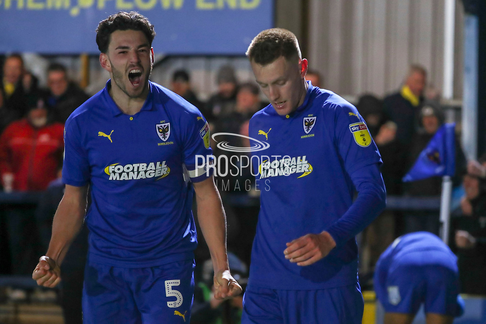 AFC Wimbledon defender Will Nightingale (5) celebrating after AFC Wimbledon striker Joe Pigott (39) scores a penalty during the EFL Sky Bet League 1 match between AFC Wimbledon and Peterborough United at the Cherry Red Records Stadium, Kingston, England on 12 March 2019.