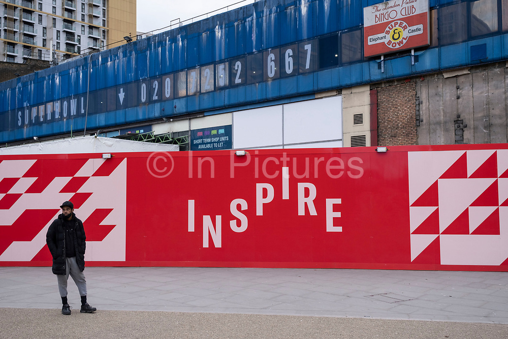 People pass a hoarding with the word inspire surrounding the now closed down Elephant and Castle shopping centre which is due for demolition on 5th March 2021 in London, United Kingdom. The area is now subject to a master-planned redevelopment budgeted at £1.5 billion. A Development Framework was approved by Southwark Council in 2004. It covers 170 acres and envisages restoring the Elephant to the role of major urban hub for inner South London.
