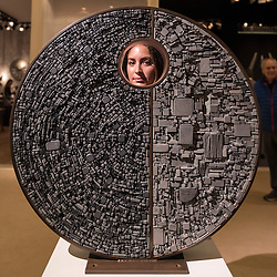 """© Licensed to London News Pictures. 29/06/2016. London, UK.  A staff member looks through """"Paradox"""" by Tom Stogdon, a stainless steel disc covered in hot bronze cut slate, at the preview, in Chelsea, of Masterpiece London, the leading international fair for art and design from antiquity to the present day with works from 154 world-renowned exhibitors on sale.  The fair is open until 6 July.Photo credit : Stephen Chung/LNP"""