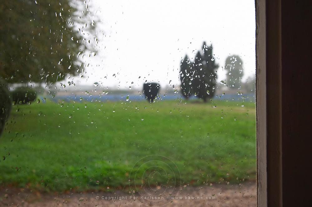 A view through a window over the park garden vineyard, rain drops on the window in focus the garden out of focus. Chateau de Cerons (Cérons) Sauternes Gironde Aquitaine France