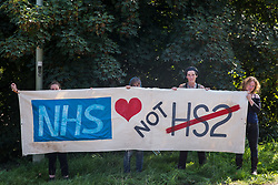 West Hyde, UK. 14th September, 2020. Environmental activists from HS2 Rebellion stand holding a NHS Not HS2 banner close to the South Portal site for the HS2 high-speed rail link. Anti-HS2 activists blocked two gates to the same site for the controversial £106bn rail link, one remaining closed for over six hours and another for over nineteen hours.