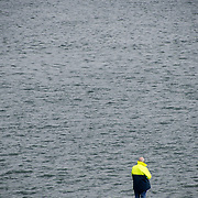 A man fishes in Beaumaris on the island of Anglesey of the north coast of Wales, UK. Copyspace with the water.