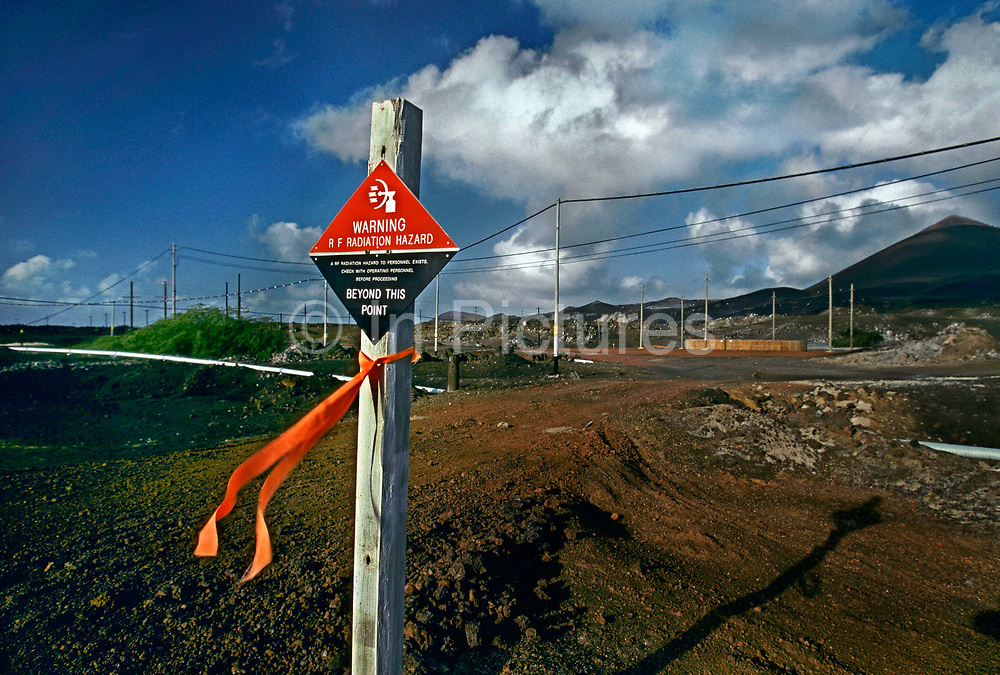 Danger warning sign for the high radio frequency radiation levels near the arials, 27th May 1997, on Ascension, a small area of approximately 88 km² isolated volcanic island in the equatorial waters of the South Atlantic Ocean, roughly midway between the horn of South America and Africa. It is governed as part of the British Overseas Territory of Saint Helena, Ascension and Tristan da Cunha. Organised settlement of Ascension Island began in 1815, when the British garrisoned it as a precaution after imprisoning Napoleon I on Saint Helena. In January 2016 the UK Government announced that an area around Ascension Island was to become a huge marine reserve, to protect its varied and unique ecosystem, including some of the largest marlin in the world, large populations of green turtle, and the islands own species of frigate bird. With an area of 234,291 square kilometres 90,460 sq mi, slightly more than half of the reserve will be closed to fishing.