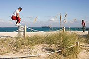 A young man finishes his exercise routine by jumping on and off a tall litter bin on South Beach Miami.
