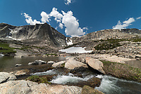 In a cirque at 10,000 feet in the Cloud Peak Wilderness during the middle of summer, it's pretty much paradise. There are no trails here, visitors must navigate their own route on steep boulder fields. Not knowing exactly what to expect is what makes it an adventure. At this elevation it never gets hot and some snowfields stay year round. Waterfalls and wildflowers abound under towering granite walls. 9 named lakes fill this high valley, plus countless unnamed tarns like this one. Each lake is different. One of them was still partially frozen, another had islands, and one a sandy beach perfect for swimming. It's the only place I've ever caught a fish with my bare hands. This was the easiest of the 3 creeks I waded through that day. The puffy cumulus clouds were a precursor to the thunderstorms that pop up most summer afternoons. Up here above treeline it's very exposed to the weather. I made it down to the protection of the forest before the first rumbles of thunder, but didn't escape getting rained on.