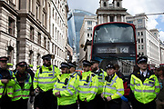 Met Police wait to arrest and clear climate change activists from the Extinction Rebellion group who are blocking the street at Bank in the heart of the City of London financial district in protest that the government is not doing enough to avoid catastrophic climate change and to demand the government take radical action to save the planet, on 25th April 2019 in London, England, United Kingdom. Extinction Rebellion is a climate change group started in 2018 and has gained a huge following of people committed to peaceful protests.