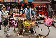 """A vender sells fruit from a bicycle in Kathmandu, Nepal. Kathmandu, the largest city in Nepal (700,000 people), is sometimes called """"Kantipur"""". The city stands at an elevation of 6235 feet / 2230 meters."""